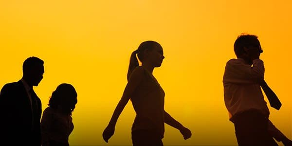 Photograph of woman walking confidently in silhouette against a bright sunset background