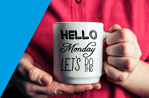 Photograph of a hands holding a mug with slogan 'Hello Monday Let's Do This'