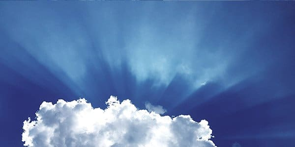 Photograph of sunlight shining from behind a cloud in a blue sky