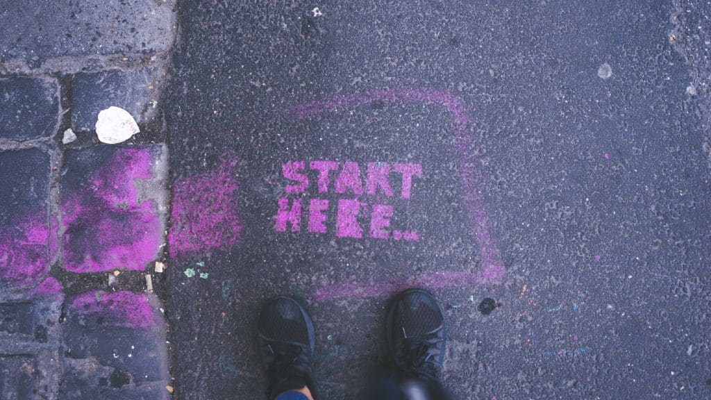 Photo of a graffiti stencil on a pavement which reads Start Here