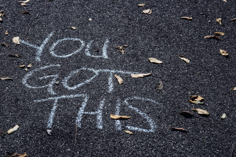 """YOU GOT THIS"" written in large letters in chalk on the pavement"