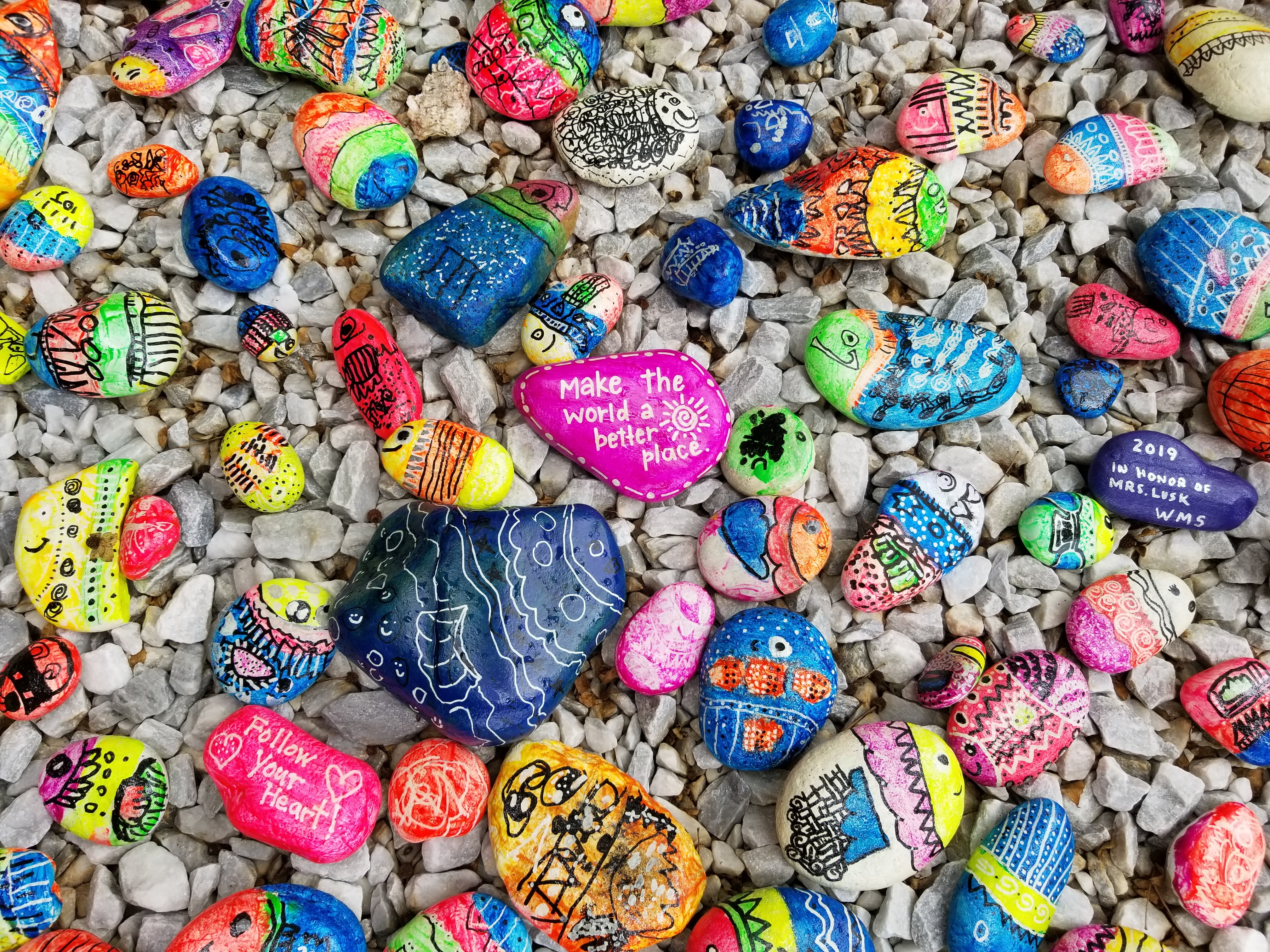 Pebbles painted with colourful messages of kindness