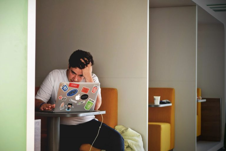 Stressed man working on a laptop