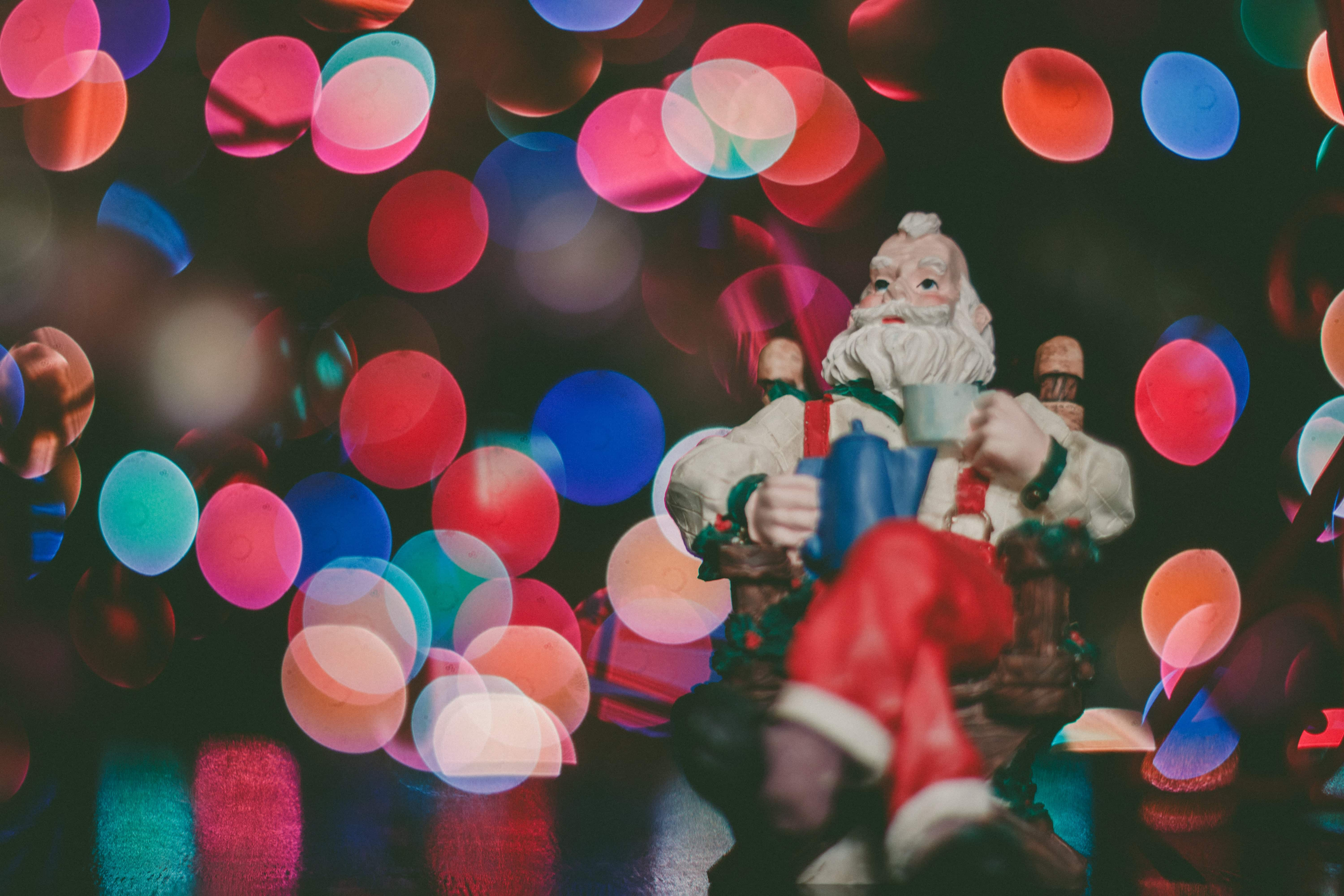 Closeup photo of lights on a christmas tree with a santa tree decoration in the foreground
