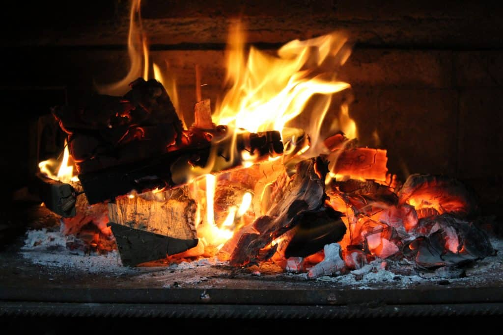 Photograph of a glowing log fire burning in a fire place