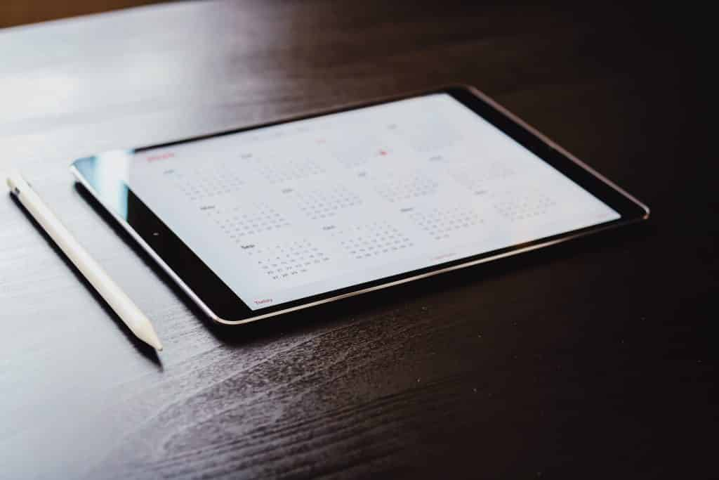 Photo of tablet sitting on desk with calendar app on screen