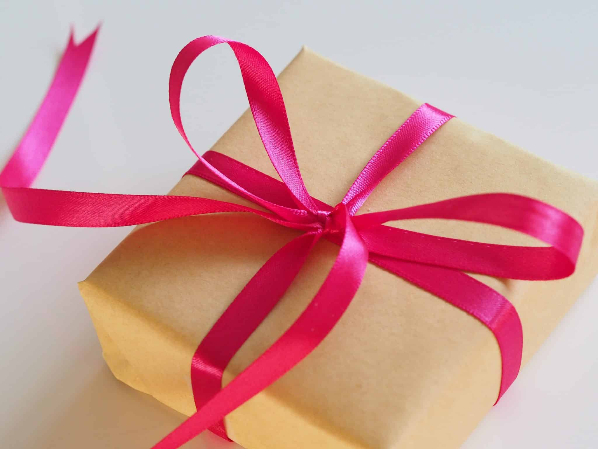 Photo of a wrapped gift with a bright pink ribbon