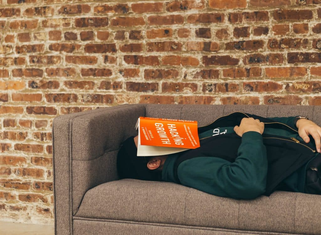 Man who has fallen asleep on the sofa with a book over his face