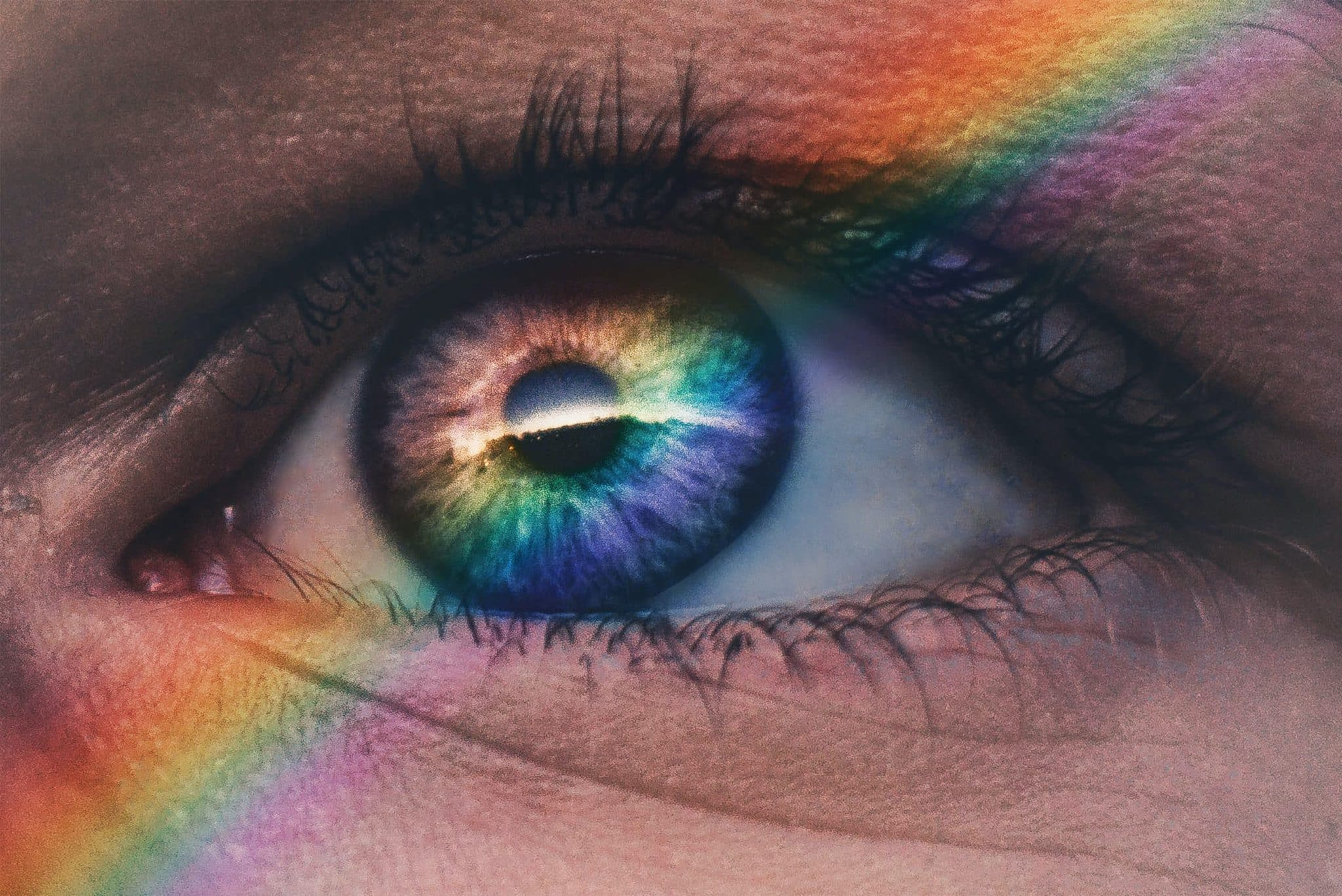Photo of an eye looking out at a rainbow